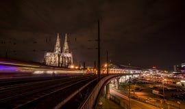 La cattedrale di Colonia alla notte con il treno di S-Bahn Fotografie Stock