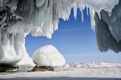 La caverne de glace blanche bleue avec des stalactites de glaçon, le ciel bleu et la pierre ont couvert la glace photos stock