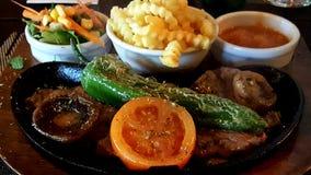 La cazuela asada a la parrilla de la carne de la chuleta sirvió con pimienta, la seta, la ensalada, las patatas y la salsa asadas Fotografía de archivo libre de regalías