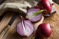La cebolla roja o púrpura cortó por la mitad, tabla de cortar el pan de madera, toalla de lino, cuchillo, tabla de cocina por la  Imagen de archivo libre de regalías