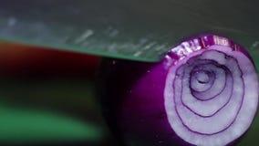 La cebolla se está tajando en los anillos con el cuchillo afilado en la tabla de cocina verde almacen de video