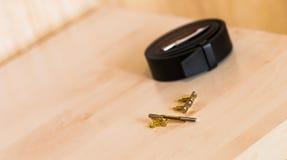 La ceinture en cuir et les boutons de manchette des hommes sur la table Les accessoires des hommes Photo stock