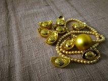 La celebración china del Año Nuevo con la decoración, los lingotes del oro y las perlas de oro representan el lujo y la prosperid Fotos de archivo