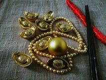 La celebración china del Año Nuevo con la decoración, los lingotes del oro y las perlas de oro representan el lujo y la prosperid Imagenes de archivo