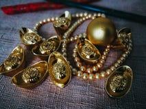 La celebración china del Año Nuevo con la decoración, los lingotes del oro y las perlas de oro representan el lujo y la prosperid Imagen de archivo