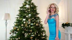 La celebración del Año Nuevo, la muchacha habla por el teléfono móvil, joven, mujer atractiva en vestido de noche cerca de un árb almacen de video