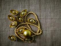 La celebrazione cinese del nuovo anno con la decorazione, i lingotti dell'oro e le perle dorate rappresentano il lusso e la prosp Fotografia Stock