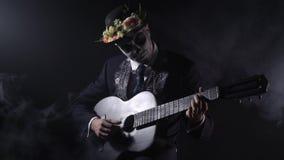 La celebrazione di Santa Muerte un uomo con trucco in bianco e nero sta giocando la chitarra video d archivio