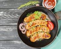 la cena casalinga arrostita su una pentola, il pomodoro, cipolla di appetito della salsiccia, arrostisce col barbecue rustico su  Fotografie Stock