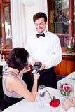 La cena en hombre del restaurante y la mujer pagan por la tarjeta de crédito Fotos de archivo libres de regalías