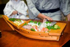 La cena japonesa tradicional sirvió en un barco de madera fotos de archivo