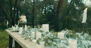 La cena romantica è servito per due nelle decorazioni adorabili della foresta misteriosa nebbiosa: candele, foglie, fiori e bello archivi video