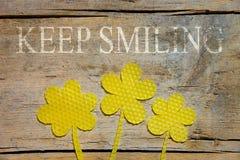 La cera de abejas, tres flores en la tabla de madera, guarda el sonreír Imagenes de archivo