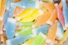La cera variopinta imbottiglia gli ossequi della caramella riempiti di bevanda dolce immagine stock