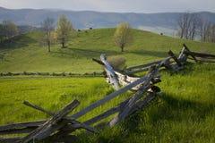 La cerca de carril derramada cruza el pasto de la montaña. Imagen de archivo