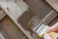 La cerca de madera con la pintura vieja resistida recibe la nueva protección de madera con un esmalte marrón foto de archivo