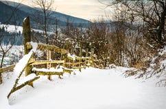 La cerca de madera del paisaje del invierno en montañas del invierno se acurruca adentro Fotos de archivo