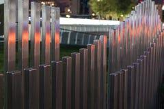 La cerca de madera ondulada cerca del camino en los colores de los semáforos de coche fotografía de archivo