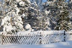 La cerca de madera se llenó por una nieve en un campo Imagen de archivo libre de regalías