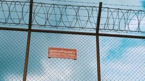 La cerca del aeropuerto del área restricta y peligros señal encima el fondo del cielo nublado almacen de metraje de vídeo