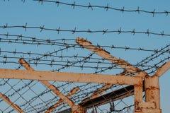 La cerca del alambre de púas en fondo del cielo azul Fotos de archivo