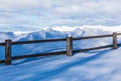 La cerca o el seto y los montones de la nieve en el campo o en el pueblo en el día de invierno frío fotografía de archivo