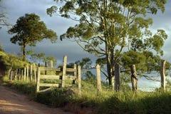 La cerca y el camino de tierra encendidos maravillosamente Foto de archivo libre de regalías