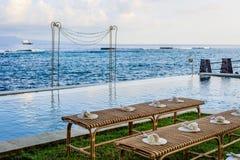 La ceremonia de boda puso cerca del océano en la puesta del sol - bancos de la rota para las huéspedes con las fans del pétalo de Fotografía de archivo libre de regalías