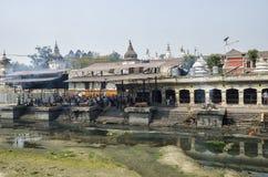 La ceremonia de la cremación a lo largo del río santo de Bagmati en Bhasmeshvar Ghat en el templo de Pashupatinath en Katmandu Imagen de archivo