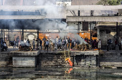 La ceremonia de la cremación a lo largo del río santo de Bagmati en Bhasmeshvar Ghat en el templo de Pashupatinath en Katmandu Imágenes de archivo libres de regalías