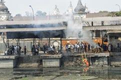 La ceremonia de la cremación a lo largo del río santo de Bagmati en Bhasmeshvar Ghat en el templo de Pashupatinath en Katmandu Fotos de archivo libres de regalías