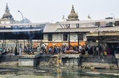 La ceremonia de la cremación a lo largo del río santo de Bagmati en Bhasmeshvar Ghat en el templo de Pashupatinath en Katmandu Imagen de archivo libre de regalías