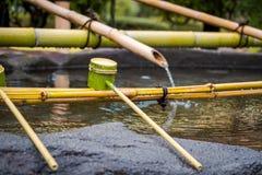 La ceremonia de limpiamiento sintoísta de Omairi usando el agua en la cucharada de bambú entra antes al templo en Japón foto de archivo