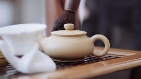 La ceremonia de té china, con la caldera limpia los descensos del agua hirvienda con un cepillo del té metrajes
