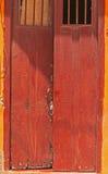 La cereza coloreó la puerta antigua manchada con las barras en las ventanas, abiertas Foto de archivo