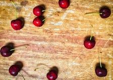 La cereza roja fresca de la baya arregla en el fondo de madera Fotos de archivo libres de regalías