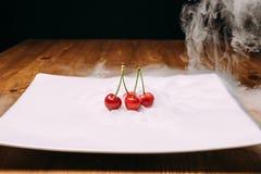 La cerise fraîche s'étend sur la glace d'un plat blanc et monte Photographie stock
