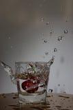 La cerise tombe avec une éclaboussure dans l'eau Photographie stock