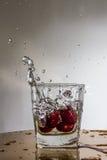 La cerise tombe avec une éclaboussure dans l'eau Image libre de droits