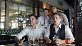 La cerveza de la bebida de cuatro hombres de negocios de los amigos y disfruta metrajes