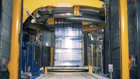 La cerveza de las botellas está consiguiendo envuelta con el material de embalaje por un mecanismo de la fábrica metrajes