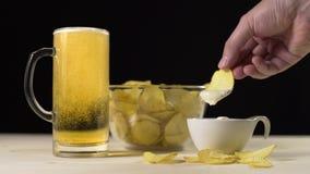 La cerveza de oro se vierte lentamente al vidrio, hombre toma las patatas y las inmersiones fritas ellas en la salsa, bocados par metrajes