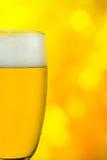 La cerveza en un vidrio en centelleo amarillo detrás enciende el fondo Imagenes de archivo