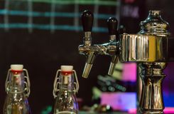 La cerveza golpea ligeramente en fila en el restaurante o el pub cerca de las botellas de cerveza vacías Fotografía de archivo libre de regalías