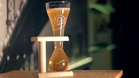 La cerveza ligera de la élite se está vertiendo en un vidrio curvado metrajes