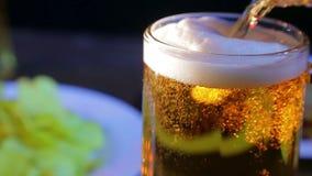 La cerveza ligera en un fondo negro se vierte en una taza de cristal almacen de video
