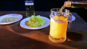 La cerveza ligeramente espumosa se vierte en una taza de cristal en una tabla de madera contra un fondo negro almacen de video