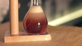 La cerveza oscura de la élite se está vertiendo en un vidrio curvado metrajes