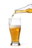 La cerveza que es vierte sobre un vidrio Foto de archivo libre de regalías