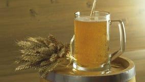 La cerveza se vierte en un vidrio contra la perspectiva de un barril y de un manojo de trigo Oktoberfest metrajes